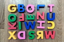 A jumble of colorful letters on a wooden table