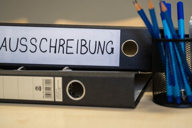 "Folder on a desk with word ""Ausschreibung"" on it, meaning call"