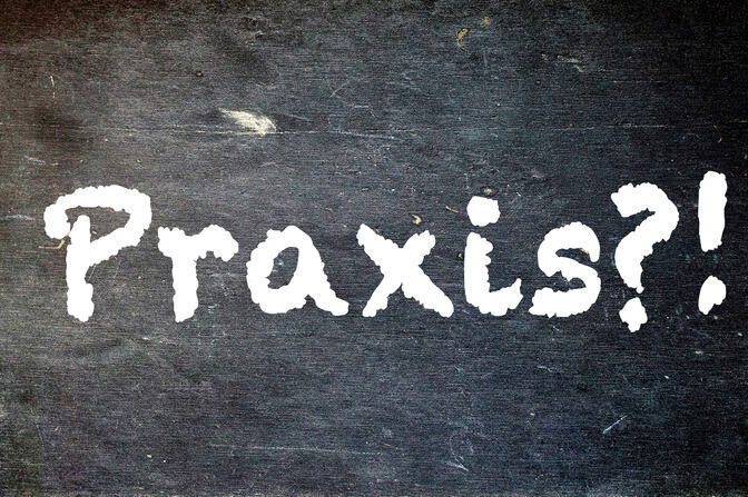 "A blackboard showing the word ""Praxis?!"", meaning practical work"